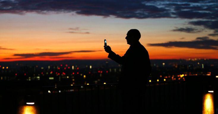 20151220 - Homem usa o telefone celular para registrar uma foto do pôr-do-sol na cidade de Dresden, na Alemanha. PICTURE:Christof Stache/AFP