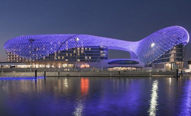 Yas Viceroy Hotel, Abu Dhabi, United Arab Emirates -- The structure consists of a pair of 12-story towers joined by a sweeping, 700-foot curvilinear skin of glass and steel—actually 5,800 pivoting, diamond-shaped glass panels that reflect the sky by day and are illuminated up by an LED system at night. #BudgetTravel #BethGreenfield