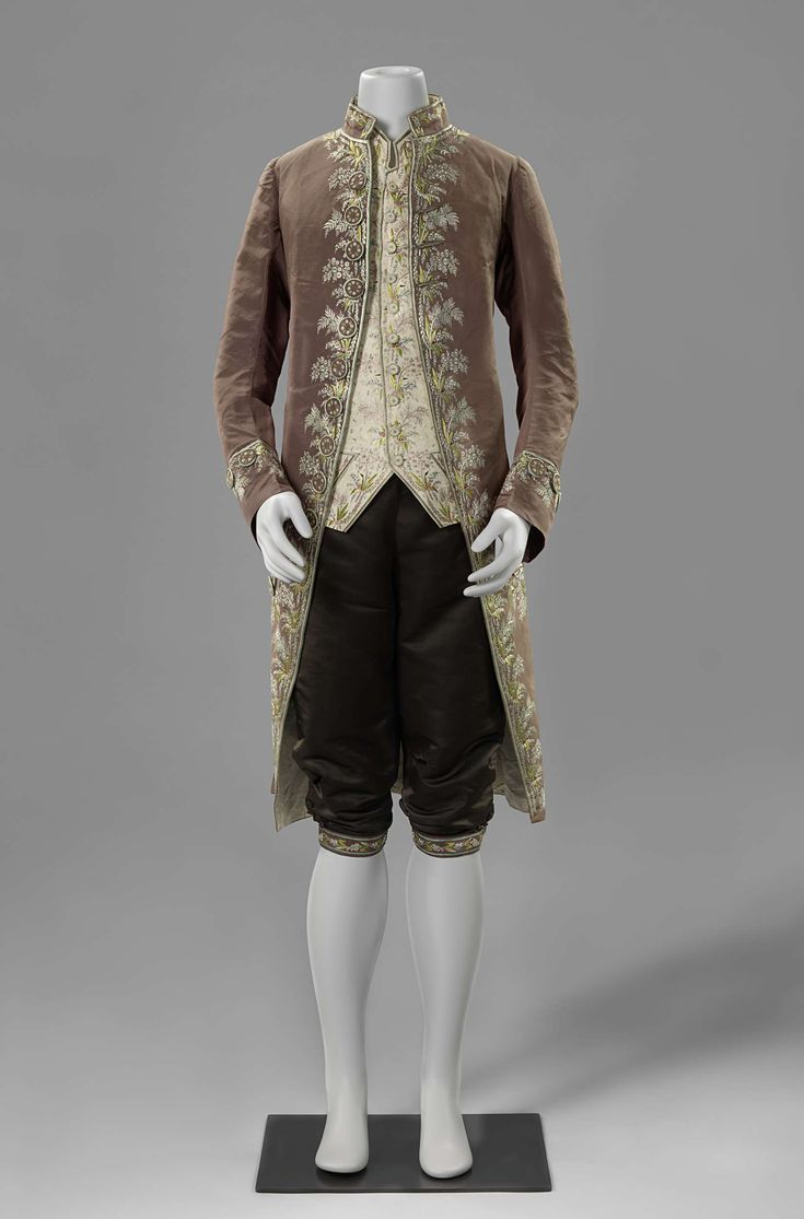 3-piece suit, probably The Netherlands, 1775 - 1800. Liver-colored silk, richely embroidered with a floral motif in multicolored silk, fabric-covered and embroidered buttons; waistcoat: cream silk with similar embroidery; breeches: black silk satin, bands with similar embroidery.