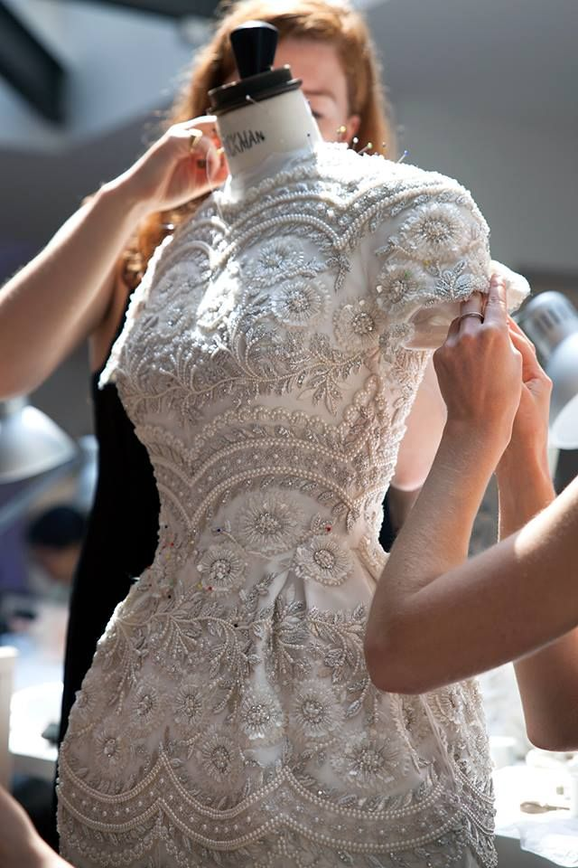 runwayandbeauty:  Ralph & Russo Haute Couture Fall 2015-16.Behind the scenes: Couturiers apply the finishing touches to an intricate ivory and silver tulle mini dress with metallic thread-work and pearl embellishment.