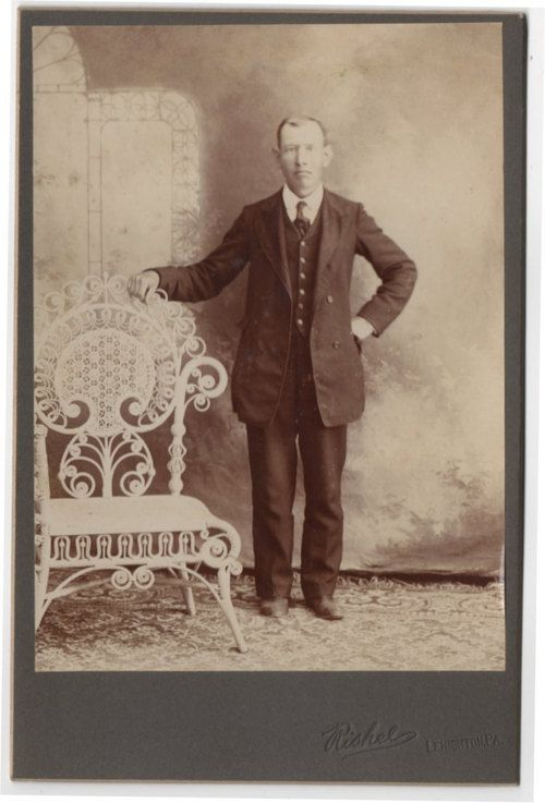 vintage cabinet photo of a short gentleman standing by a tall and fancy wicker chair