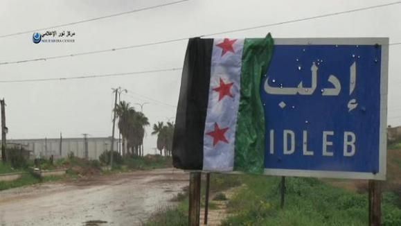 SYRIA and IRAQ NEWS: #Kobane Update 70 - The Islamic State broke through Kurdish lines at the weekend to link up with their surrounded fighters, but the Kurds are fighting back hard. In #Idlib Opposition fighters are setting up a new administration but threatening if bombs fall they will also bomb Alawite enclaves. *For More #Iraq and #Syria News ...* http://www.petercliffordonline.com/syria-iraq-news-4 PIC: FSA Flag at Entrance to Idlib City: