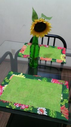 Placemat with colored burlap center over cotton floral print .