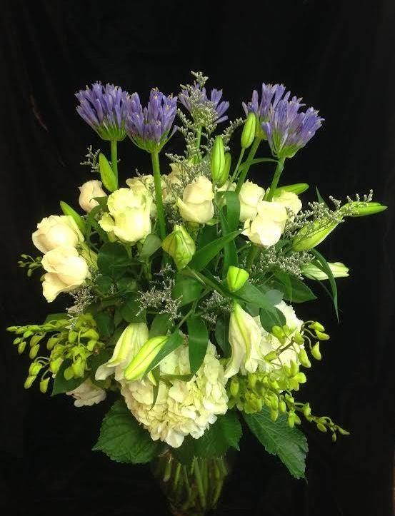 If the formal funeral flower arrangements of days gone by don't suit you, perhaps a vase arrangement would pay better tribute to the memory of your loved one. Here, the delicate yet striking blooms of lilac coloured Agapanthus are a nod in recognition to a favourite of the dearly departed -- lilacs.