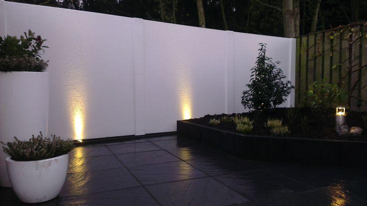 Onderhoudsvrije tuin met nieuwe kunststof witte muur staat, met extra spots die in de avond nog meer sfeer brengen.
