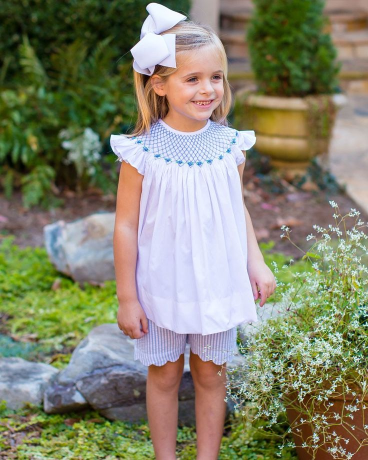 White+Smocked+Top+with+Blue+Seersucker+Scalloped+Shorts+-+White+angel+sleeved+top+with+blue+smocking+and+buttons+at+back+of+neck.+Blue+seersucker+scalloped+shorts+with+elastic+waist.+100%+cotton.+