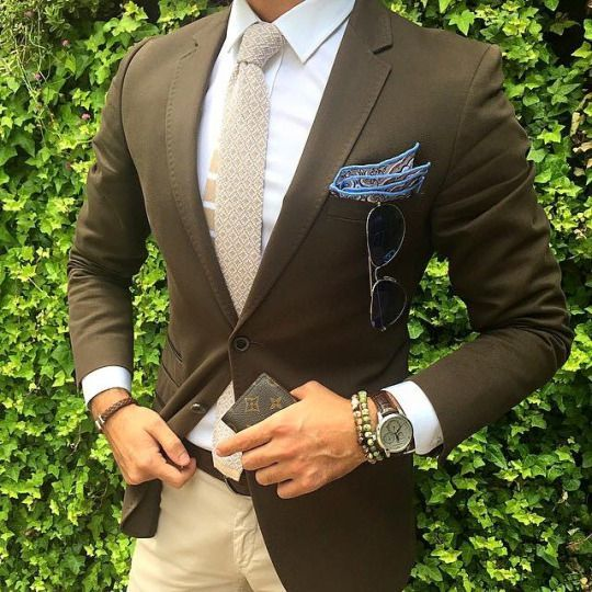 The brown jacket and blue pocket square stands out in this outfit.