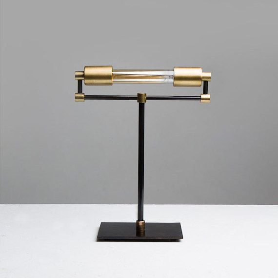 This is a very unique rendition of a bankers desk lamp. The bulb is 30 watts, making it very easy on the eyes. The lamp itself is made of brass while the base is made of steel.  This lamp looks great on a desk, counter or shelf! Also a wonderful art piece for any home.