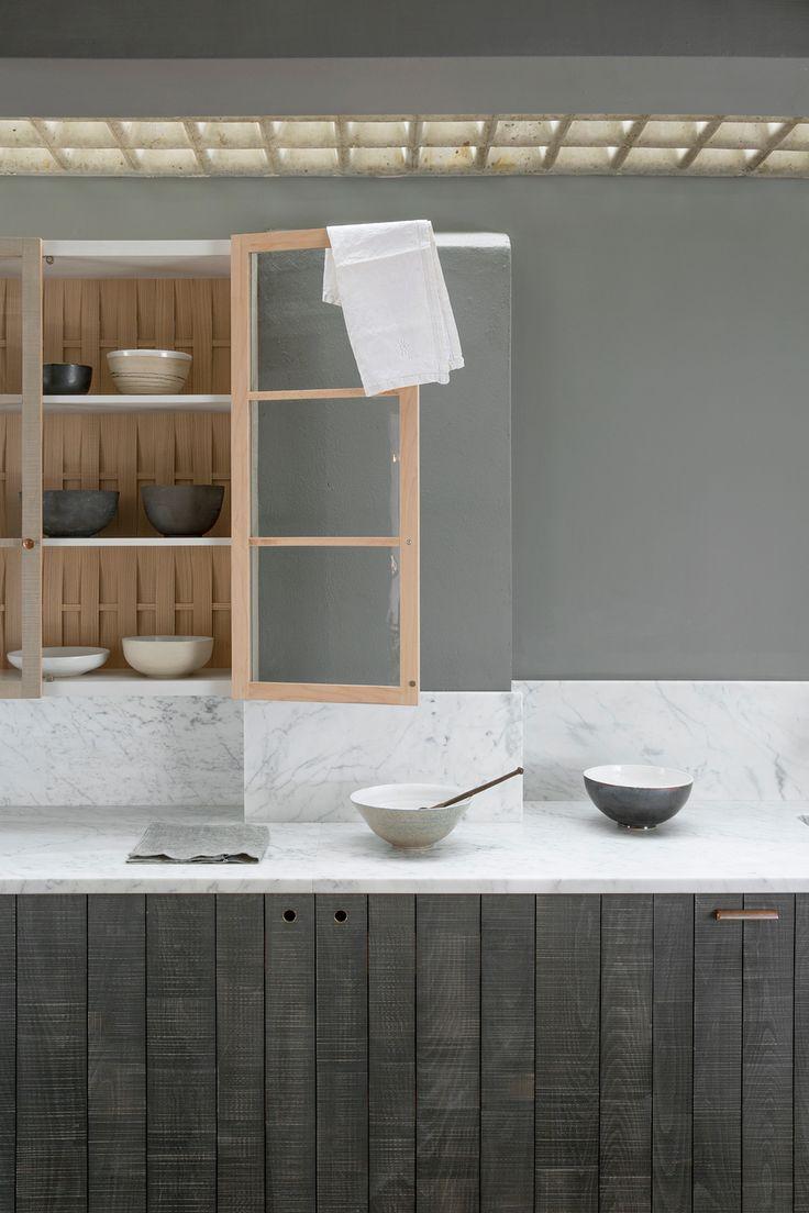 Smooth honed Carrara marble worktops, textured Sebastian Cox cabinets and handmade ceramic bowls by deVOL