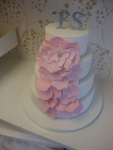 White wedding cake with pink flowers and glittering cake topper