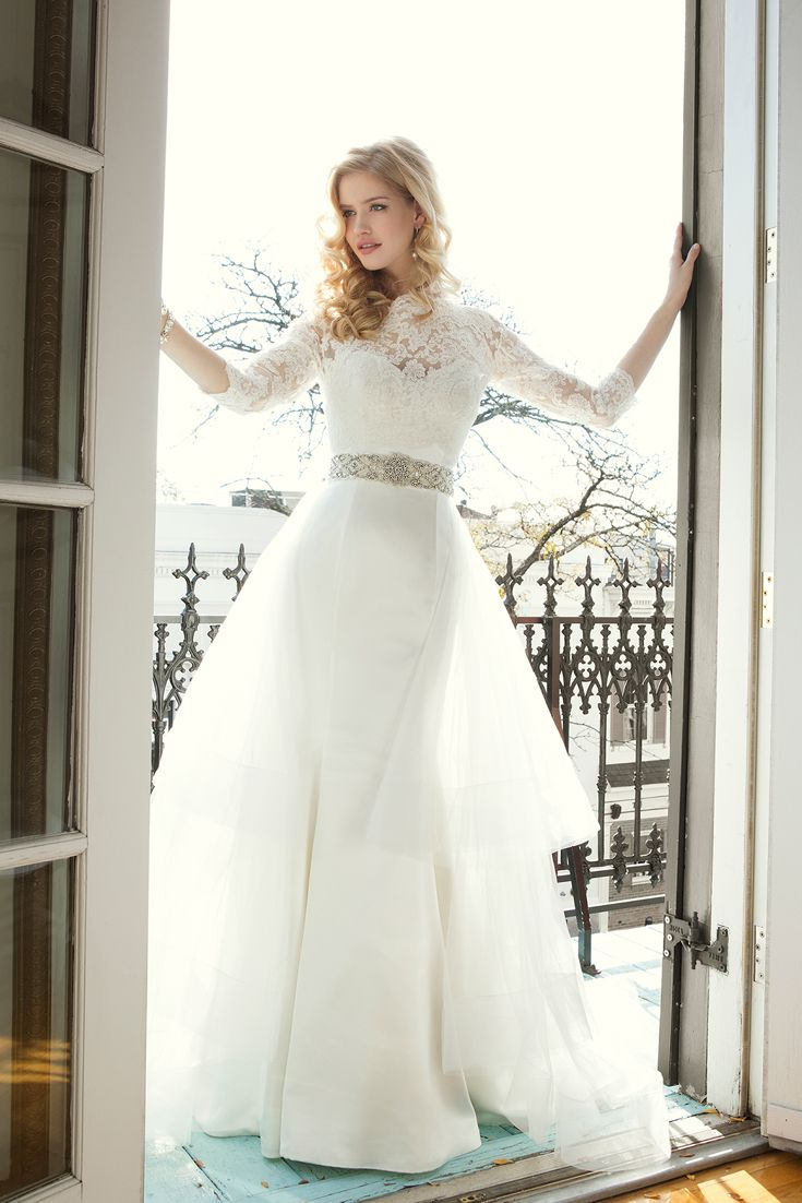 Make a statement in this mermaid wedding dress paired with a lace top and ruffle skirt. The stunning sweetheart neckline luxe charmeuse wedding dress is paired with a tulle ruffled skirt, vintage inspired lace jacket, and crystal belt. The chic combination is perfect for a bride looking to make a statement on her wedding day!