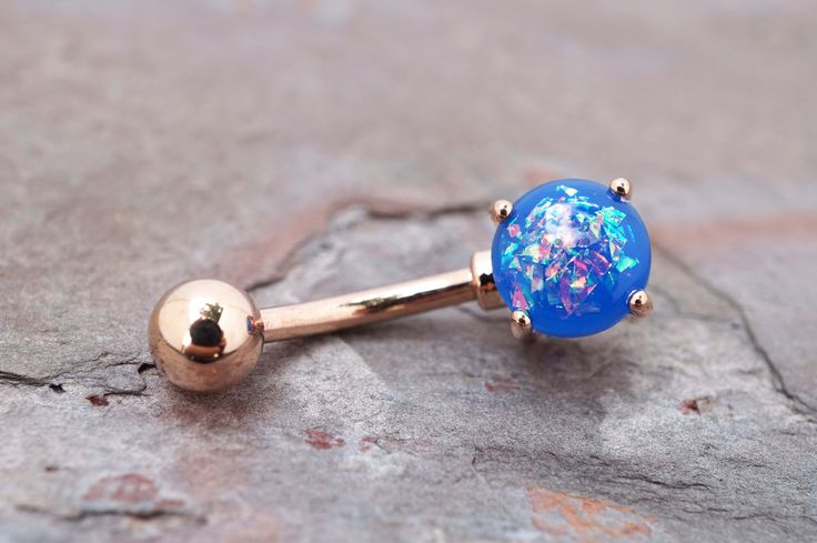 "Synthetic blue opal belly button jewelry ring. The 8mm blue opal is prong set and glows in the light with radiant iridescence. The opal belly ring is 14 gauge and 3/8"" long (10mm), and is made of IP r"