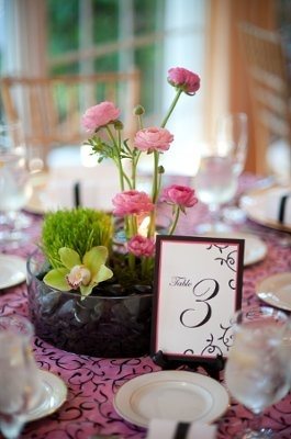 Simple centerpiece with greenery and stem of flowers in rocks on busy patterned tablecloth.