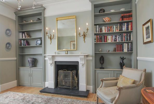 wall sconces and mirror above fireplace, built in alcove cabinets either side