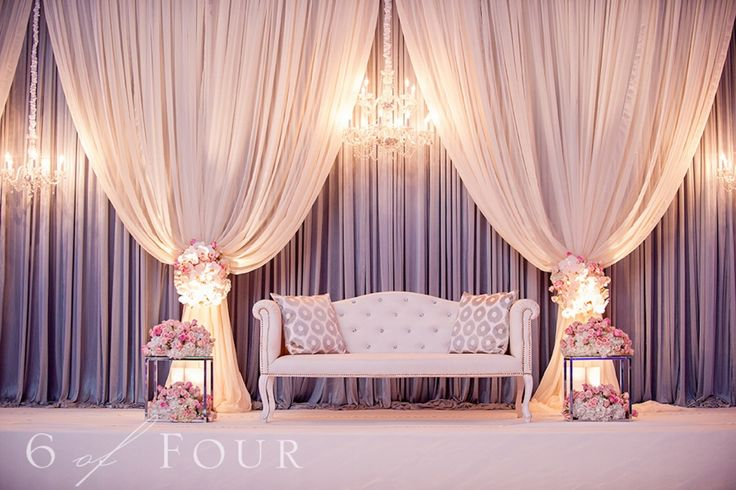 Just gorgeous decor, love the cream drapery, flowers around the drapery to tie it, and a hang crystal light. Decor for the greeting photos.