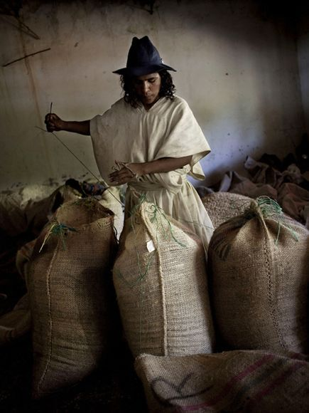 An Arhuaco man works in a coffee warehouse in the Sierra Nevada de Santa Marta. Arhuaco, believed to be descended from the Tayrona people, produce coffee in the north Colombian mountains.