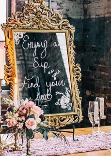 Old mirror as sign by champagne glass escort cards ... enjoy a sip, find your seat. | Photo by VUE Photography