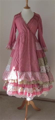 Pink and ruffly! love the cut of the top and he lond sleeves. Quilt lookingish with lace under skirts. Just perfect!
