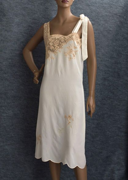 (Front) 1920s nightgown fashioned from cream colored silk crepe de chine. In addition to the beige lace on the bodice it features appliquéd clusters of lace flowers. The scalloped hem and deep side slits are finished with self binding. The nightgown ties in back at the waist.