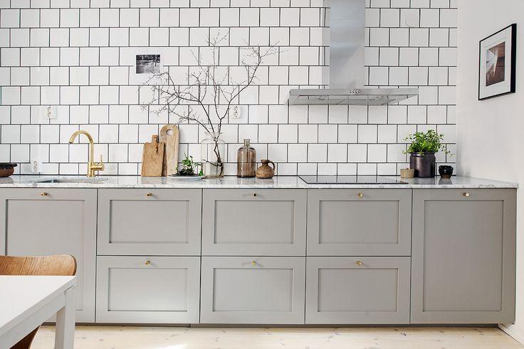 Me he enamorado de esta cocina, desde esos azulejos blancos con la lechada en negra, los muebles en color gris con tiradores y grifo en dora...