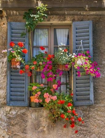 Vintage ventana con contraventanas de madera abiertas y flores frescas Foto de archivo
