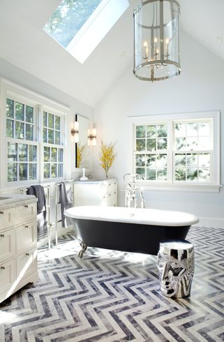 marble herringbone pattern floors, claw foot tub, towel warmers, modern sky-lit ceiling and eclectic art stool - Paul Davis Interior Design