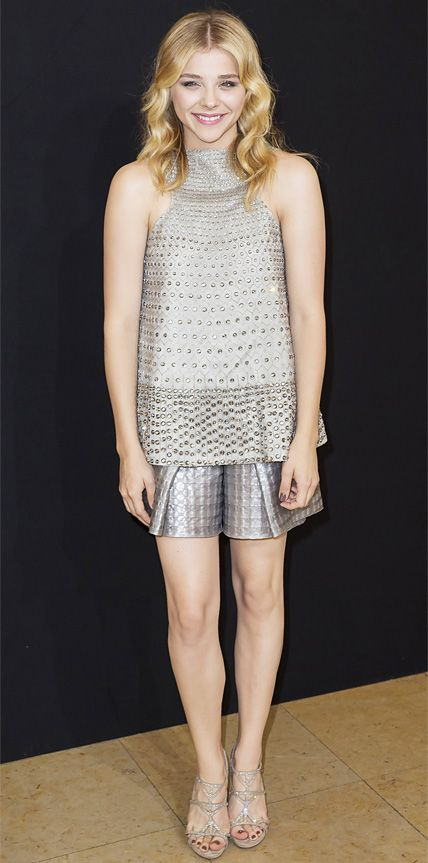 Chloe Grace Moretz glittered from the front row at the Armani Prive fall/winter 2014 show in an embellished gray halter and gunmetal textured shorts, both by Giorgio Armani, and sparkly sandals.