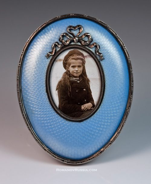 An Antique Faberge Miniature Egg-Shaped Picture Frame, St. Petersburg, 1899-1904, workmaster Hjalmar Armfelt, in pale blue guilloche enamel and gilt silver, with photograph of Grand Duchess Maria Nikolaevna on the Imperial Yacht 'Standart' in 1906.