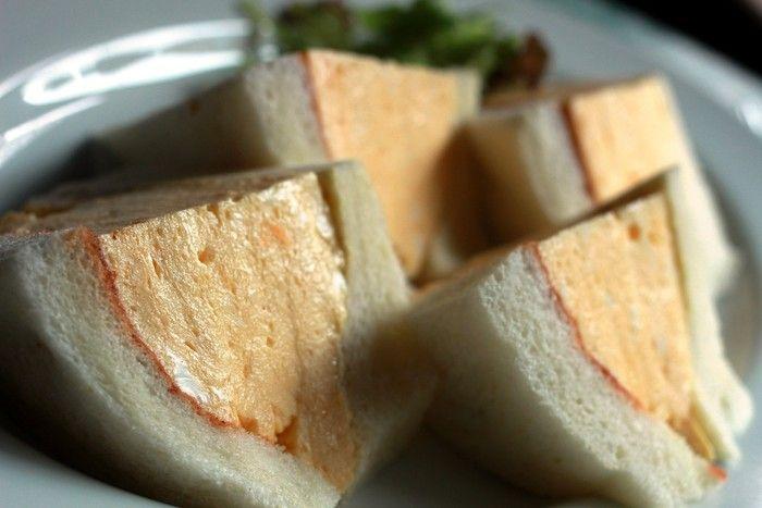 こちらが話題の卵サンド!分厚い卵がぎっしりと詰まった、とってもふわふわのサンドイッチです。  パンもさっくり焼いてあり、食べやすくてボリューミー!    実はこの卵サンドは京都の中では有名な喫茶店「コロナ」の卵サンドをシェフが直伝で伝えて貰ったもの。名前はもちろん「コロナの卵サンド」。  コロナファンも唸る程の卵サンドをぜひご賞味下さい。喫茶マドラグ