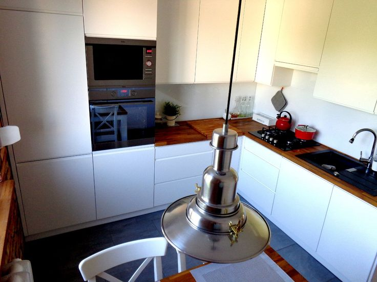 Drewniany blat i białe szafki w kuchni