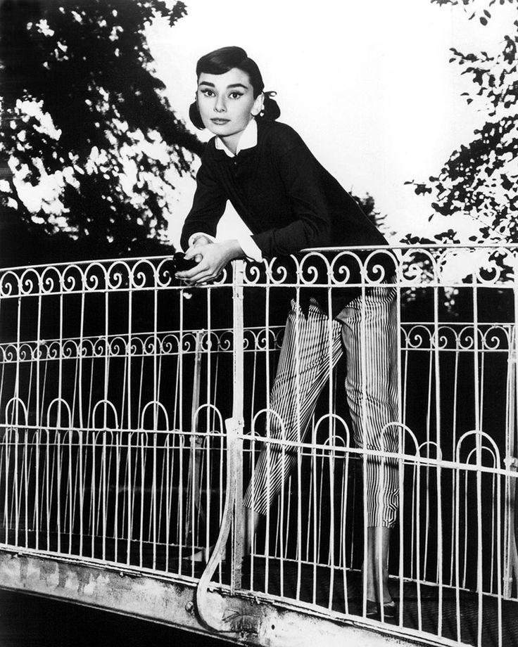 January 1953 | Audrey poses on a bridge, wearing striped crops and a dark sweater with a peter pan collar. via @stylelist