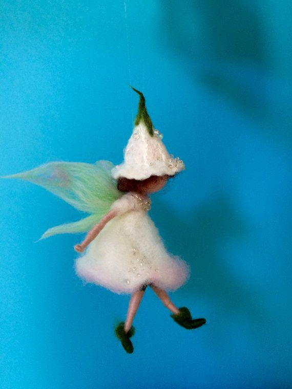 Dit is de delicate bloem fee in een witte jurk, geborduurd met glanzende kralen. Haar cap in de vorm van een bloem bud is ook geborduurd met kralen.