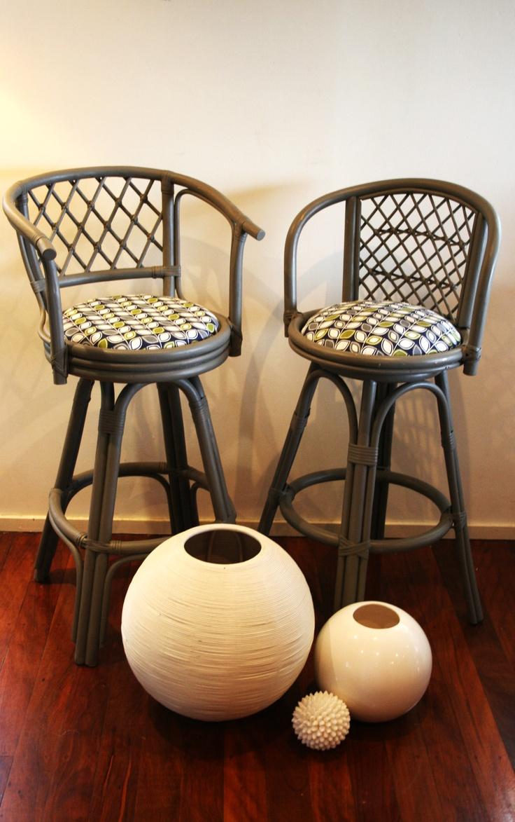 Orla Keily style fabric on retro grey cane stools and spherical vases.