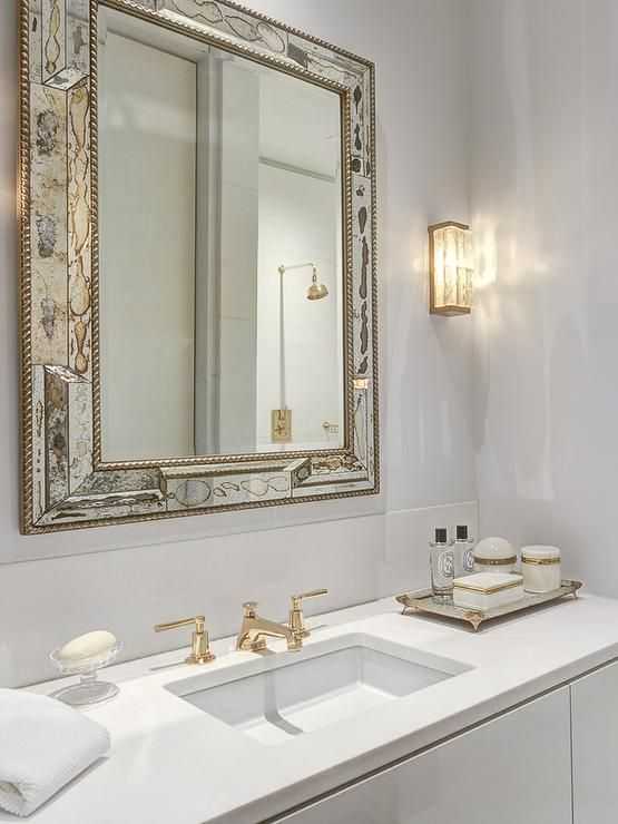 White And Gold Bathroom Features An Antiqued Mirror Beveled Mirror Over A White Washstand Topped