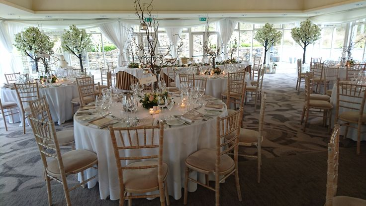 Chiavari chairs, cherry blossom trees. candlelight and floral centerpieces