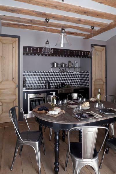 Cuisine avec un camaïeu de gris sur les murs, poutres, parquet et portes en bois