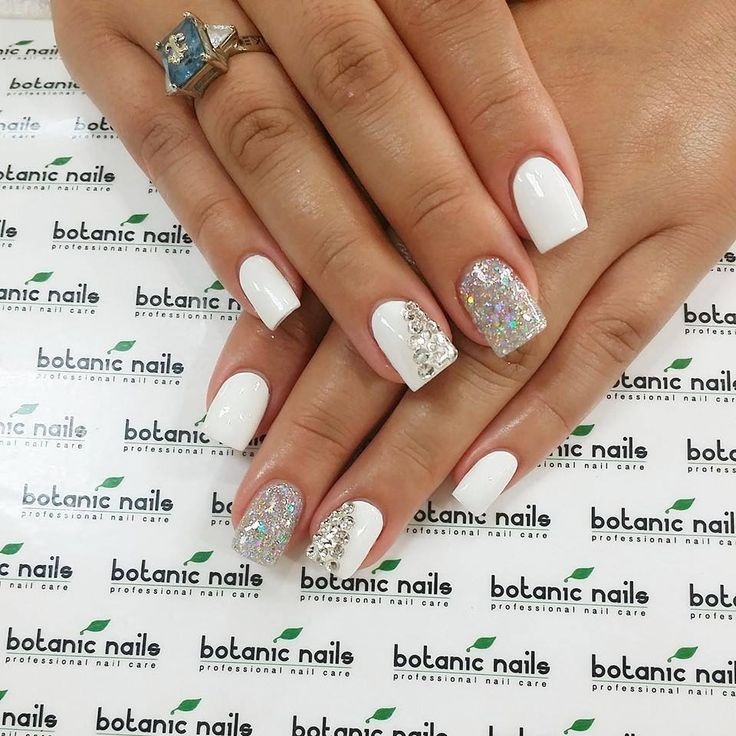 White nails with a silver accent nail and a white accent nail with gems on a diagonal