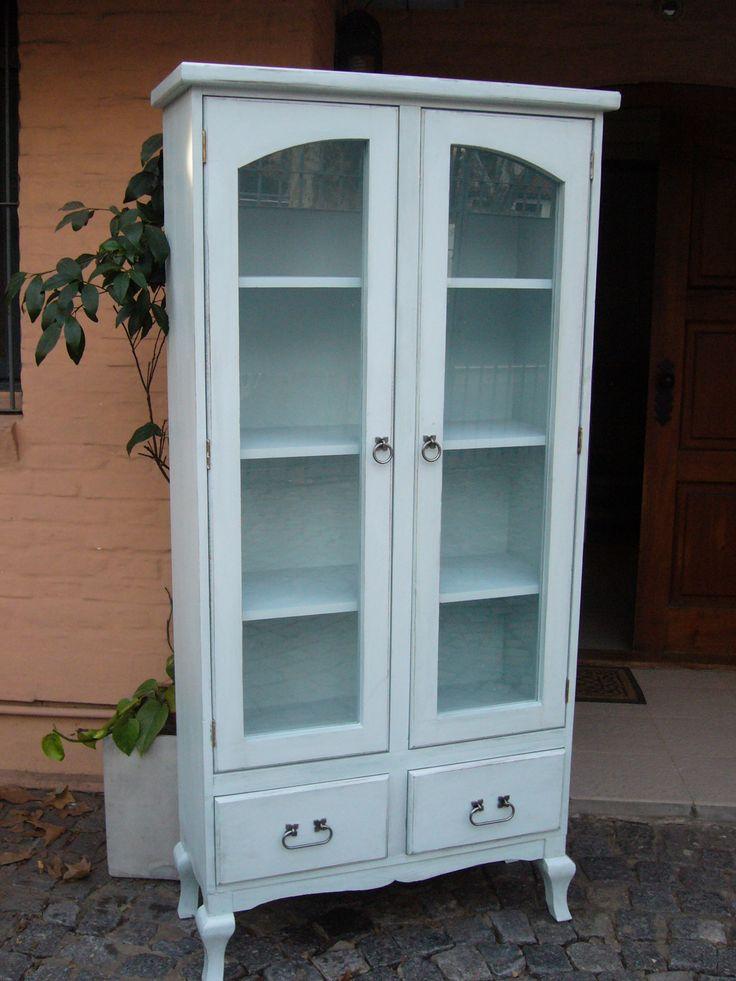 Mueble en madera maciza pintado y con terminación en técnica decapado. Dos puertas largas con vidrio y tres estantes. Dos cajones amplios. El mueble termina con patas estilo provenzal. Herrajes artesanales color gris metal. Color Celeste Hielo en stock (Se puede realizar en otros colores a elección). Medidas: 0.80m x 1.70m x 0.30m.