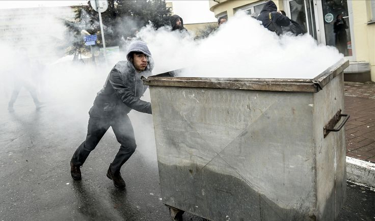 A Turkish protester pushes a garbage container during clashes with riot policemen outside Okmeydani Hospital in Istanbul on March 11, 2014. Violent protests erupted between police and hundreds of protesters outside the hospital where a teenager, who had fallen into a coma after being hit by a tear gas canister during mass anti-government protests last year, died. AFP PHOTO/BULENT KILIC (Photo credit should read BULENT KILIC/AFP/Getty Images)