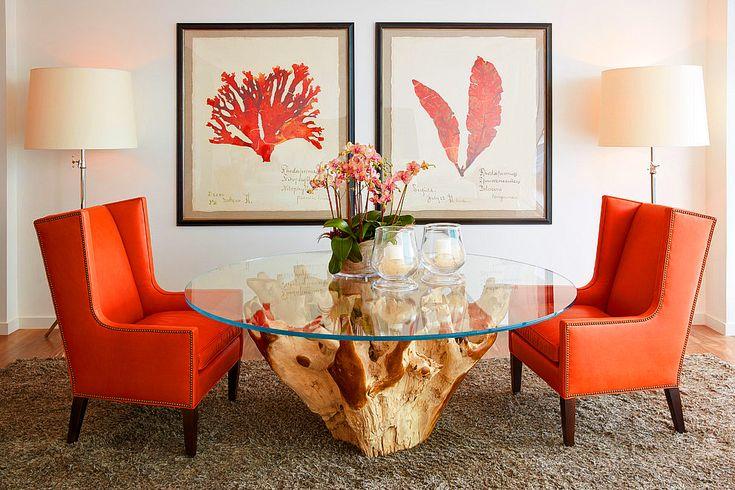 Светлые стены гостиной комнаты, оригинальный стол, строгие кресла с кораллового цвета обивкой и тематические мелочи в виде картин, цветов, свечей