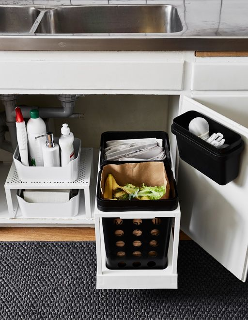 The space under the kitchen sink is updated with new storage that allows waste separation for recycling. On the right side two bins on a movable rail add functionality. To the left a shelf insert doubles storage space.