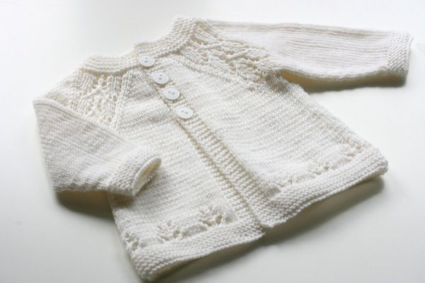 Кофточка для новорожденных с ажурными линиями реглана и низа вязаная спицами