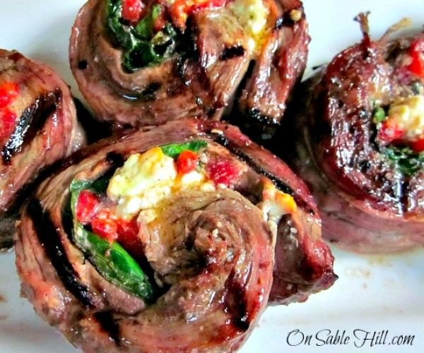 Flank steak stuffed with spinach, feta cheese and roasted red pepper, then rolled up, sliced and grilled.