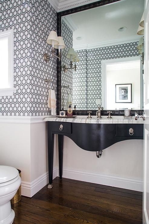 David Hicks Hexagon Wallpaper is patterned in a bathroom featuring a black footed, curved vanity, with silver drop ring pulls, paired with a gray and white marble countertop.