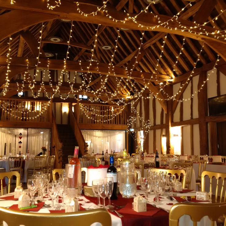 A beautiful canopy in warm white fairy lights draped from beam to beam with draped fairy lights over the balcony. #barnwedding #weddinglighting #fairylights #buckinghamshire #eventprofs @thetudorbarnweddings