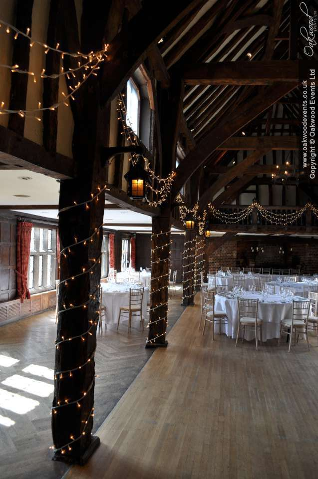 Simple wound pillars with swags of fairy lights. Venue: Great Fosters Tithe Barn. Lights by Oakwood Events