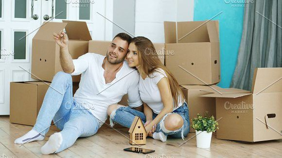 Happy Couple Sitting On Floor In New House Young Man Give Keys To