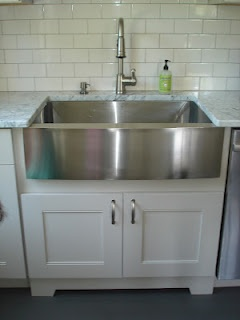 White cabinets with stainless apron sink, and white subway back splash.  Just what I'm thinking.