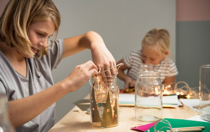 A boy makes a lantern with a jar, coloured paper and a string of lights