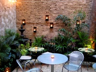 Small courtyard design with wall mounted candles - great little patio space.